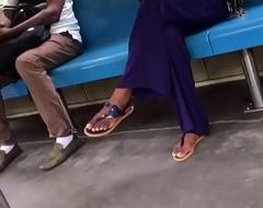 Sunbathe girl crossed toes in skim through flops